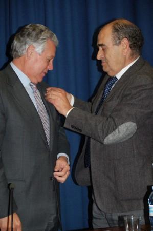 El director del IES Nuestra Señora de los Remedios, Juan Coronel, impone la insignia del centro al consejero de Gobernación, Francisco Menacho.