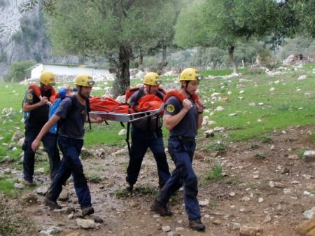 Bomberos del parque de Ubrique trasladan en camilla al excursionista herido.