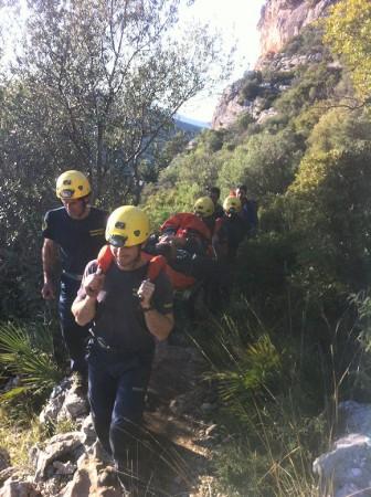 Los bomberos trasladan al accidentado en camilla.