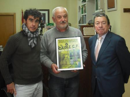 El alcalde, con el cartel del partido de fútbol, con el consejero externo del Cádiz, Miguel Cuesta, y el concejal de Deportes, Víctor Chaves.
