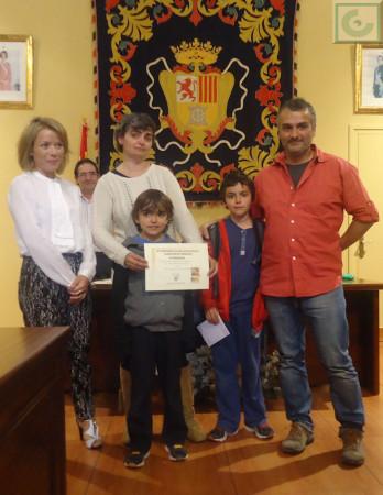 Carmen Montesdeoca y David Menacho, con sus hijos, reciben el primer premio de manos de la concejal Remedios González.