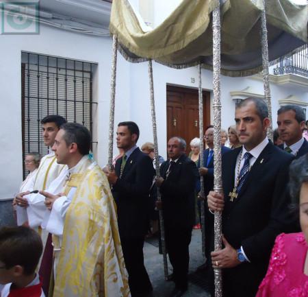 Los sacerdotes y miembros de la hermandad, con el palio.