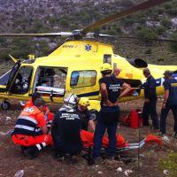 Bomberos y sanitarios atienden al accidentado para trasladarlo en helicóptero al hospital.