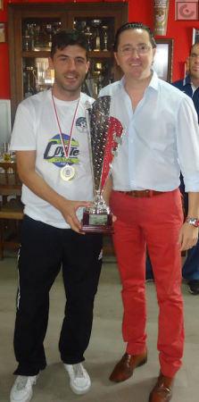 El capitán del Estudiantes, José Antonio Bohórquez, con el trofeo de campeón, y el presidente de la Peña Sevillista, Juan Luis Ríos.