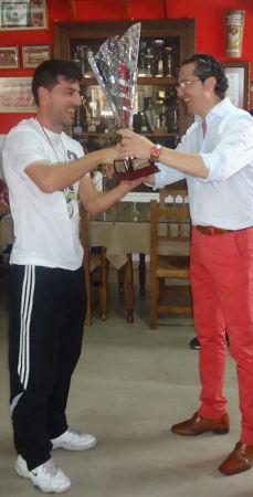 El presidente de la Peña entrega el trofeo de campeón al capitán del Estudiantes.