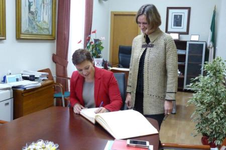 La delegada de Fomento de la Junta, Gemma Araujo, firma en el libro de honor del Ayuntamiento, en presencia de la alcaldesa, Isabel Gómez.