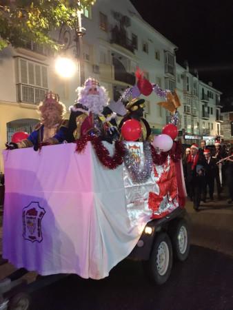 La carroza de los Reyes Magos de la Peña Sevillista, seguida por la Agrupación Musical Ubriqueña, por Los Callejones.