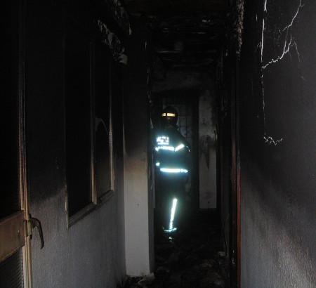 Uno de los bomberos en el interior de la vivienda siniestrada.
