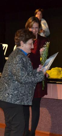 La alcaldesaentrega un ramo de flores a una de las descendientes de una componente de la directiva de Renacer.