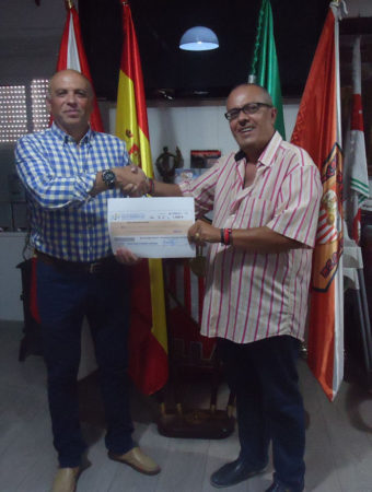 El presidente de la Peña Sevillista, Manuel Sígler, entrega el premio correspondiente a la persona que vendió la papeleta que resultó agraciada, Jesús Reina.