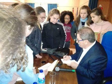 El autor firma ejemplares ante las alumnas.