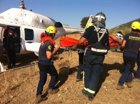 Bomberos del grupo de rescata en montaña de Ubrique trasladan al parapentista herido en la sierra de Líjar.