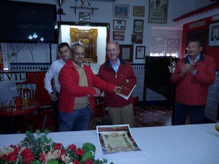 El presidente de la Peña Sevillista de Ubrique, Miguel Bautista, entrega un ejemplar del libro 'Pasión a flor de piel' al representante de la peña de Lebrija.