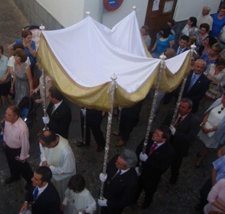 El párroco, Ildefonso González, bajo palio. Detrás, el alcalde, Manuel Toro.