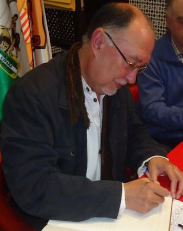 Juan Castro firma en el Libro de Honor de la Peña Sevillista de Ubrique.