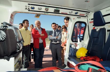 Los representantes de las administraciones observan el interior de un helicóptero de los servicios de emergencia.