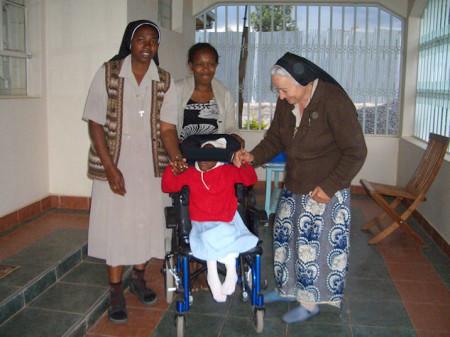 La niña keniata, en la silla de ruedas financiada por CAPI.