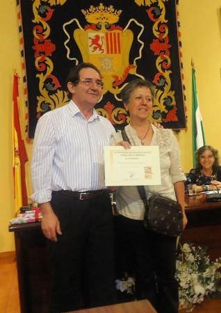 Carmen Domínguez, de la asociación de vecinos Plaza de la Verdura, recoge el segundo premio, ganado por Antonio Sergio Barragán, de manos de Vicente Romero, de la Carniceria-Charcutería La Plaza.