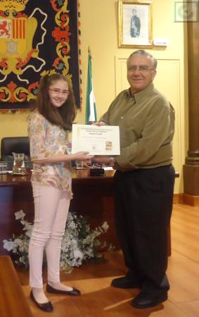 Ana Mª recibe el diploma y lote de libros del premio infantil, de manos de Aurelio López.