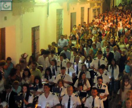 La Banda Municipal de Música y público participante en la procesión.