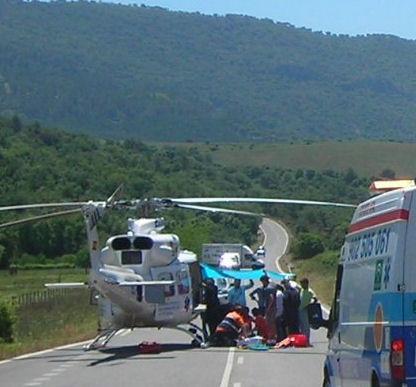 Sanitarios atienden al herido, ante un helicóptero del 061, para su traslado al hospital.