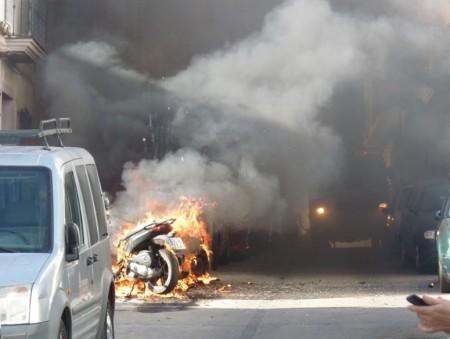 Una motocicleta ardiendo y humo provocado por el incendio.
