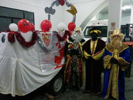 Los Reyes Magos de la Peña Sevilista, junto a su carroza, antes de iniciar su recorrido.