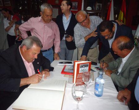 Lora firma en el libro de honor de la peña y Sanjosé rubrica una foto.