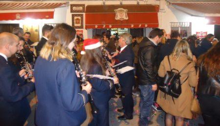 Interpretación de temas navideños de la Agrupación Musical Ubriqueña ante la sede de la Peña Sevillista.
