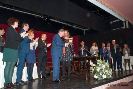 Bartolomé Pérez Sánchez de Medina recibe la insignia de Hijo Predilecto de la Villa, de manos de la alcaldesa, Isabel Gómez García, en presencia de la corporación municipal, ante un auditorio lleno (Foto: Radio Ubrique).